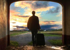 スーツケース片手に出発する男性