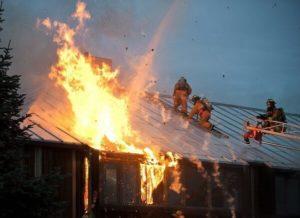 屋根の上で消火する消防士